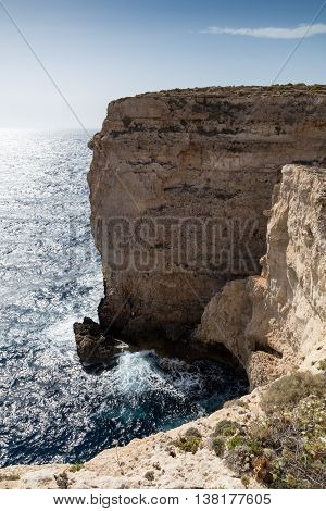 Waves smash against massive cliffs towering above the blue mediterranean sea dwarfing a lone figure. Portrait
