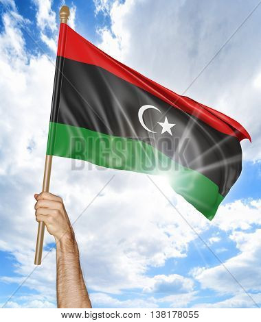 Person's hand holding the Libya national flag and waving it in the sky, 3D rendering