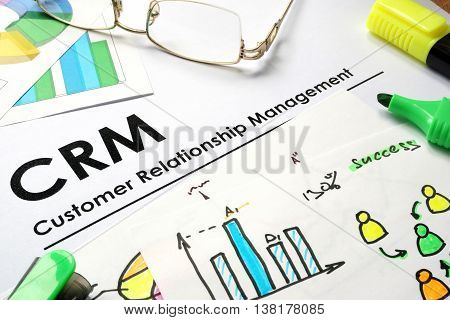 Paper with words CRM customer relationship management.