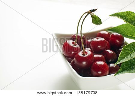 Fresh cherries in bowl on white background close up