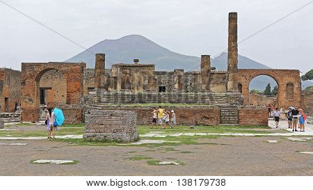 POMPEII ITALY - JUNE 25: The Temple of Jupiter With Tourists in Pompeii on JUNE 25 2014. Ancient Roman Ruins UNESCO World Heritage Site in Pompeii Italy.