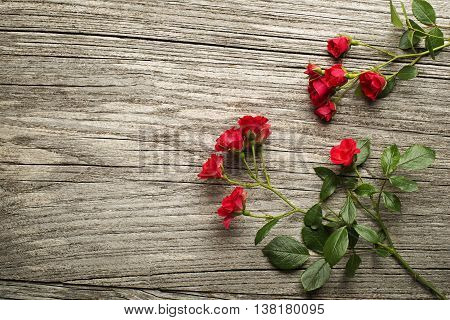 Red roses on wooden background overhead shoot