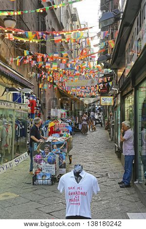 NAPLES ITALY - JUNE 25: Spanish Quarters in Naples on JUNE 25 2014. Quartieri Spagnoli With Tourists in Narrow Street at Historic Neighborhood in Naples Italy.