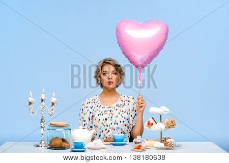 Portrait of young beautiful girl in white blouse sitting at table with sweets, looking at camera, holding pink baloon in shape of heart over blue background.