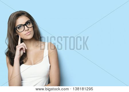 thinking woman with nerd glasses. blue background