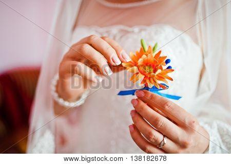 bride touch finger gerbera buttonhole at wedding