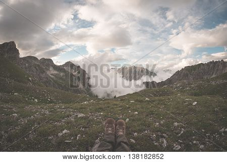 Human Feet With Hiking Boots Lying On Grass At The Top Of Alpine Valley With Scenic Clouds Glowing A