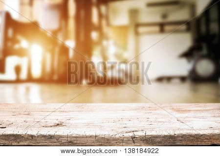 Empty wooden desk space over fitness gym background. For product display montage.