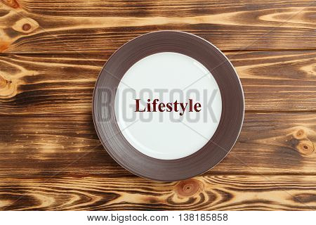 Empty brown plate on a brown wooden table, lifestyle