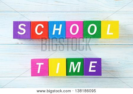 Colorful wooden toy cubes on a blue wooden background, school time