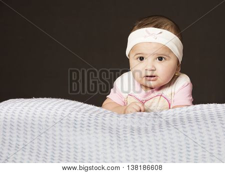 Small baby girl laying down on bright blanket
