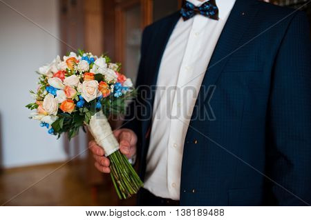 wedding bouquet at hand of groom at wedding