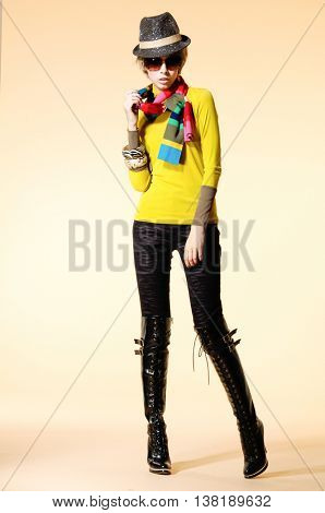 Full body fashion model in fashion clothes with,hat,posing on light background