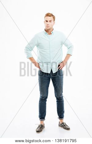 Serious suspicious young man standing with hands on hips over white background