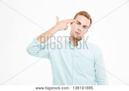 Desperate stressed young businessman with finger to his temple like a gun over white background