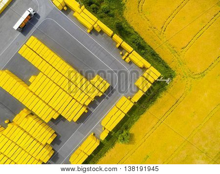Aerial view of storage and freight terminal in rapeseed field. Industrial background.
