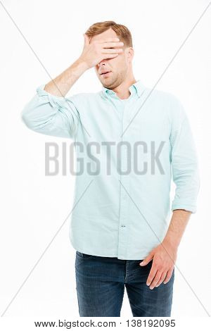 Handsome young businessman covered his eyes by hand over white background