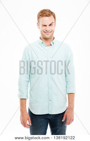 Smiling playful young man making funny face and winking over white background