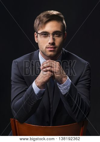 Portrait of a handsome young man looks at the camera over clasped hands.