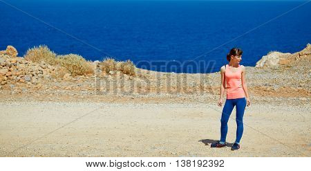 Happy woman enjoying freedom on travel in Crete coast, Greece. Female on summer or spring leisure vacation towards the sea