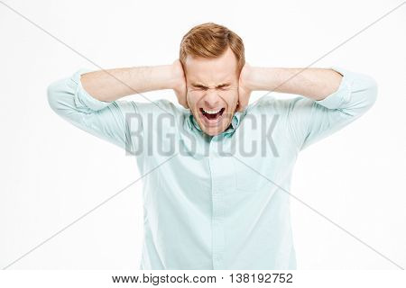 Irritated stressed young man covered ears by hands and shouting over white background
