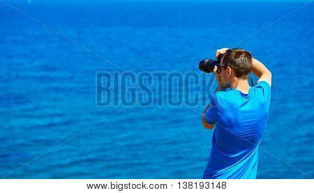 Man, traveller and photographer stands on the cliff and taking photo