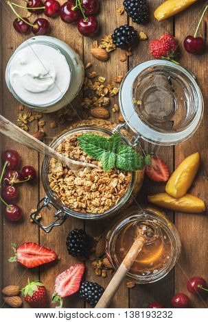 Healthy breakfast ingredients. Oat granola in open jar, yogurt and honey served with berries, nuts and fresh mint on rustin wooden background. Top view, vertical composition