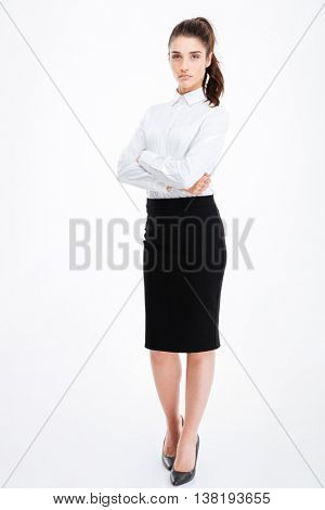 Full length portrait of a serious businesswoman standing with arms folded isolated on a white background