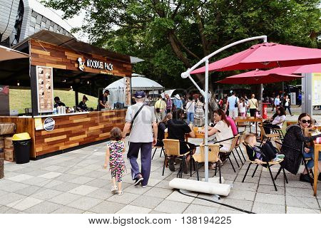 CLUJ-NAPOCA ROMANIA - JULY 10 2016: People have a snack at the Street Food Festival in front of the Cluj Arena stadium in central park Cluj. Vendors in stalls sell fast food from different cultures.