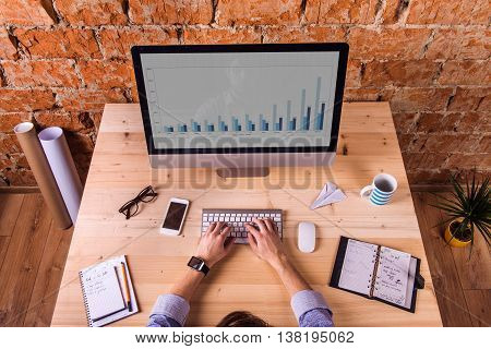 Hands of unrecognizable businessman at the desk, wearing smart watch, writing on keyboard. Computer and various office supplies around the workplace.
