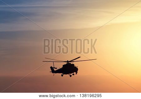 silhouette of military helicopter flying at sunset background