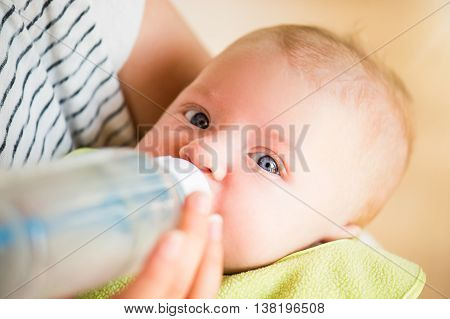 Close up of unrecognizable mother holding her baby son in the arms, feeding him with milk from bottle