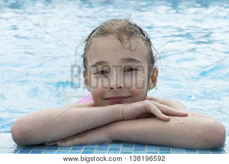 portrait of Caucasian brunette young girl of 7 - 8 years old posing in pool with hands crossed