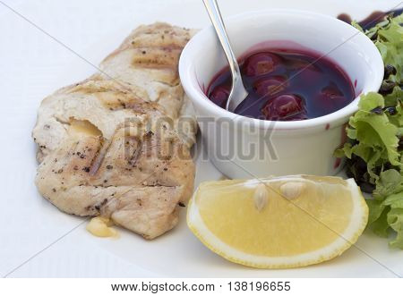 close up of fried chicken served with cherry sauce lettuce and lemon on white plate
