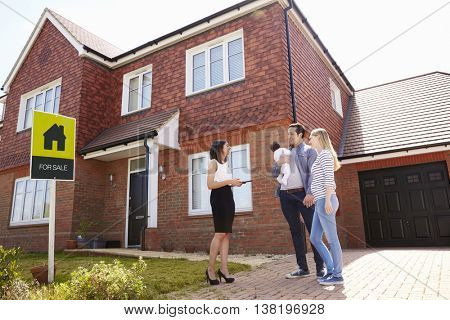 Realtor Outside House For Sale With Young Family