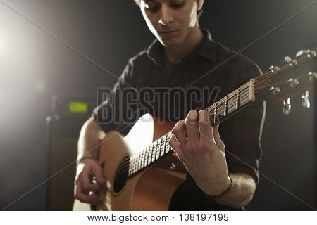 Man Playing Acoustic Guitar In Studio