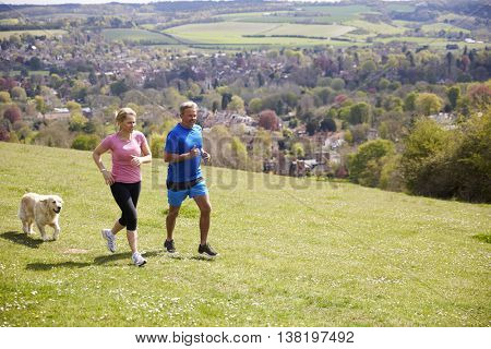 Mature Couple With Golden Retriever Jogging In Countryside
