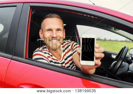 Man in car showing smart phone display smiling happy. Focus on model.