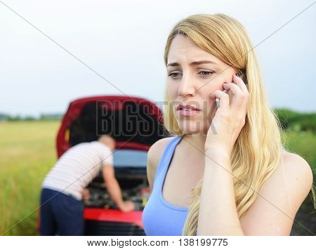 Attractive blonde woman call for help on the phone. Damage to auto. Young couple can not continue the way because of the broken car.