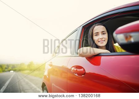 Beautiful woman in a car against the backdrop of receding into the distance the road.