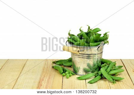 Metal bucket full of pods of green peas on a wooden background. Open the pod and peas. / isolation on a white background without shadow. / Summer. The season of harvest.