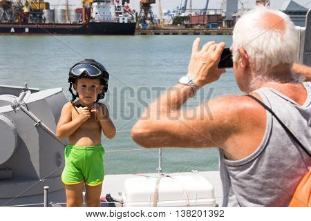 Odesa, Ukraine - July 03, 2016: Grandfather photographing a boy in a military helmet on new warship 'Akerman'. Celebration of Ukrainian NAVY forces day