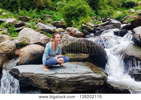 Yoga exercise outdoors -  woman doing Ashtanga Vinyasa Yoga arm balance strength training asana Tolasana - scales pose at waterfall in Himalayas