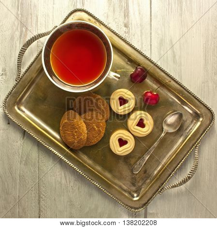 A photo of a vintage tray with a cup of tea cookies and cherries shot from above on a light wooden boards texture; tea time concept