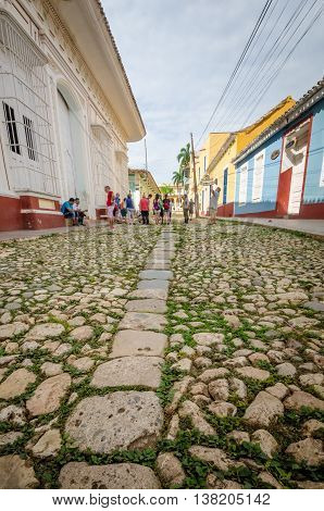 TRINIDAD - CUBA, JUNE 15, 2016: Tourists walk along a cobblestone street in the charming town with perfectly preserved colonial mansions that have been transformed into museums chronicling the history of sugar harvests and slave trade.
