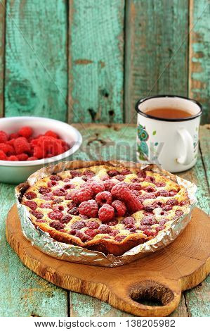 Homemade quark pie with raspberries in foil served on wooden board with green tea vertical