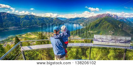 Father and his son enjoying the view to Locarno city from Cardada mountain Swiss Alps Switzerland