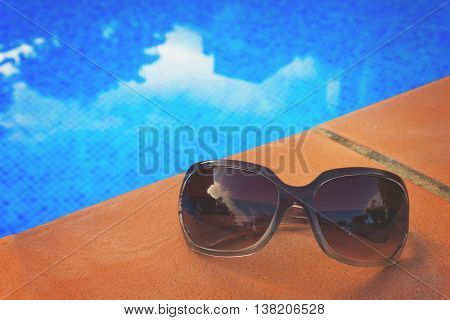 Sunglasses near blue tiled water of pool, retro toned