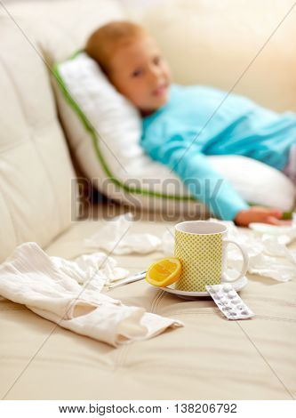 Cold boy lying on the bed in front of him as lemon tea medicines selective focus