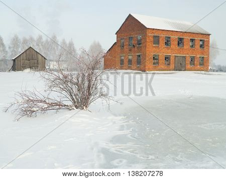Old mill house and winter frozen pond.